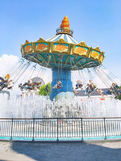Chain swing ride over fountain against blue sky at amusement park