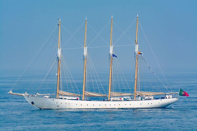 Tall ship sailing in sea against clear blue sky