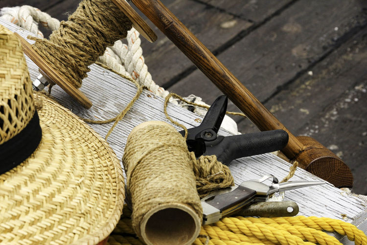 Close-Up Of Wicker Hat With Rope And Tools On Table