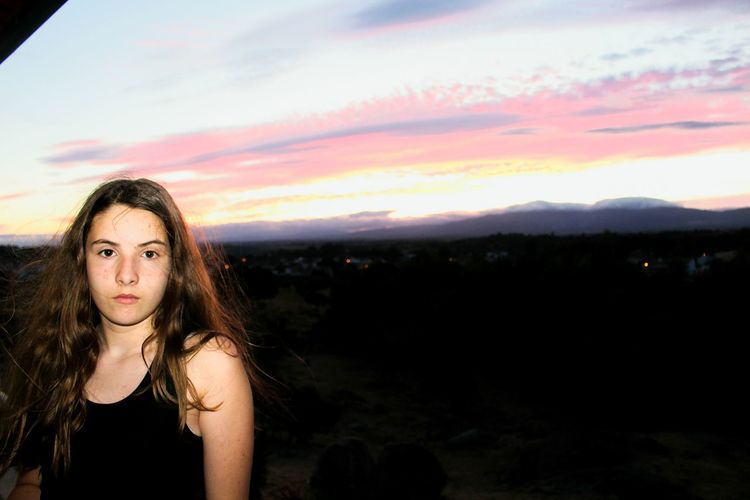 Beautiful young woman against mountains against sky