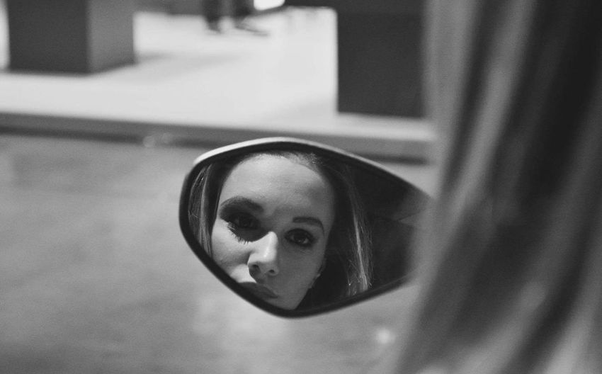 Young woman reflecting in side-view mirror of car
