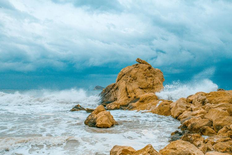 Rock On Beach Against Sky