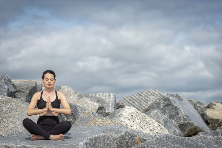 Full Length Of Woman Meditating While Sitting On Rock Against Cloudy Sky