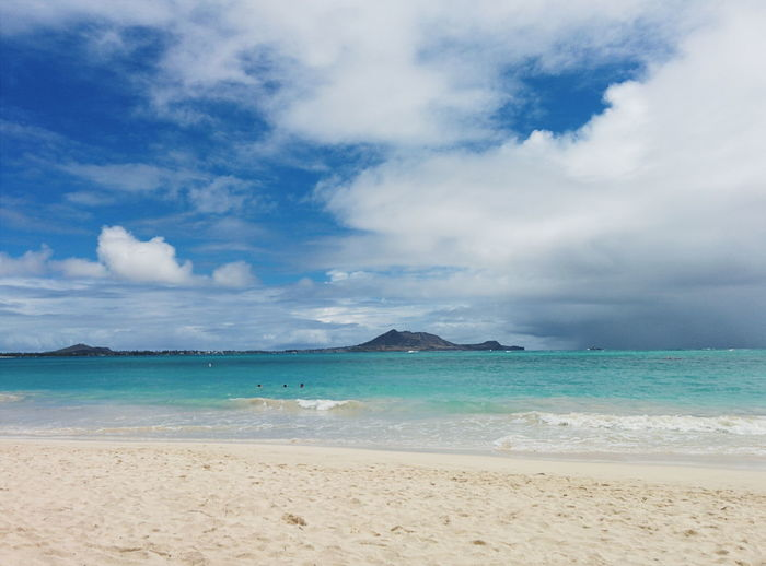 Scenic view of hawaiian beach and turquoise sea against cloudy sky