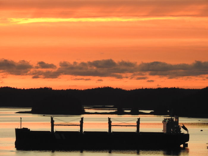 Silhouette Boats On Shore Against Orange Sky