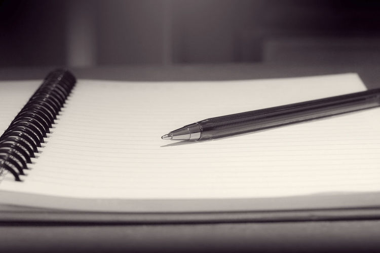 Close-up of pen with diary on table