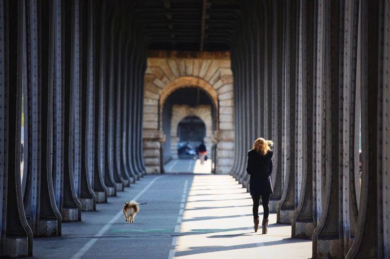 Woman with dog walking in corridor