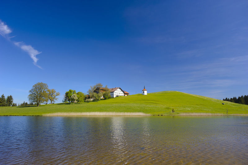 Scenic view of lake and hill against blue sky