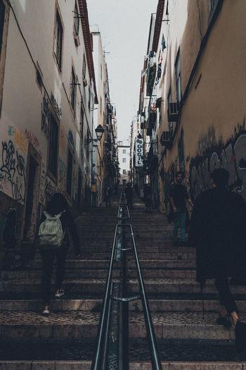 People walking on railroad tracks amidst buildings in city