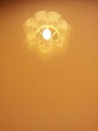 Low angle view of illuminated light bulb hanging against wall