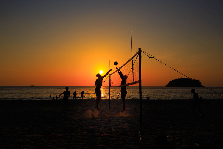 Silhouette people playing volleyball on beach against sky during sunset