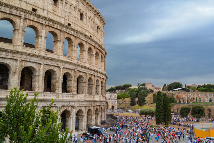 High angle view of tourists at colosseum against cloudy sky