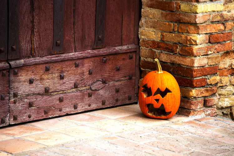 Jack o lantern outside old wooden door during halloween