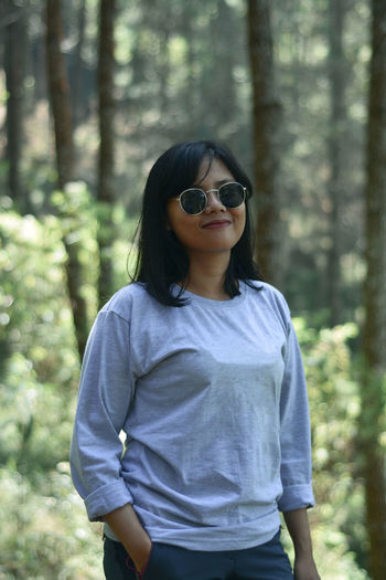 Young woman wearing sunglasses standing in forest