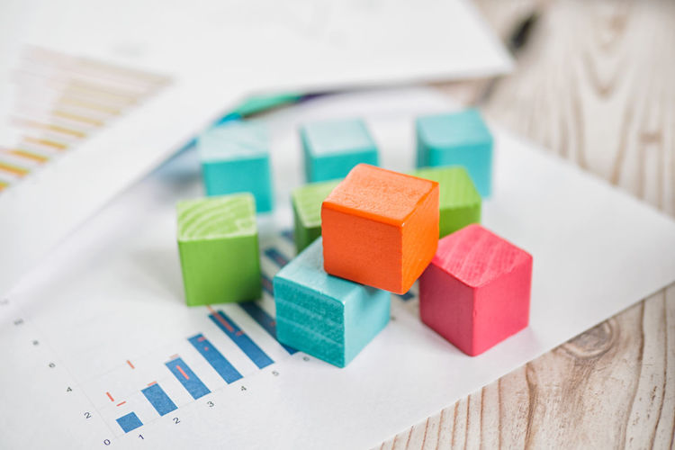 High angle view of colorful toy blocks with document on table
