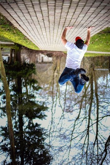 Man Doing Handstand On Footpath Against Trees