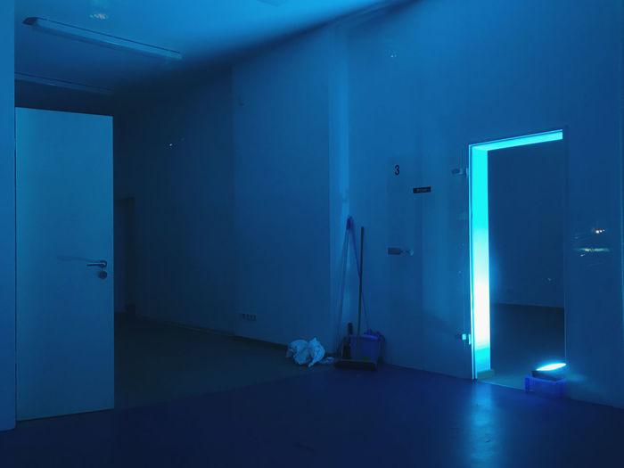Neon blue illuminated building interior, empty room at night