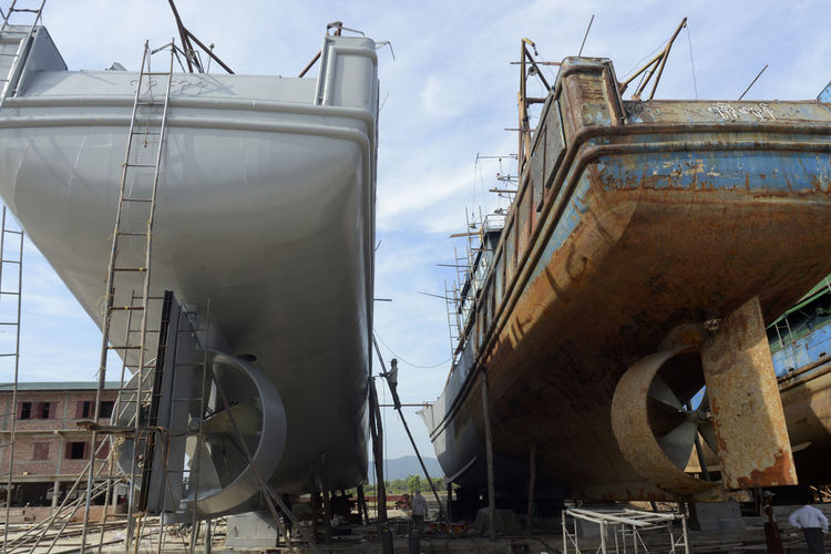 Low angle view of ships at construction site against sky