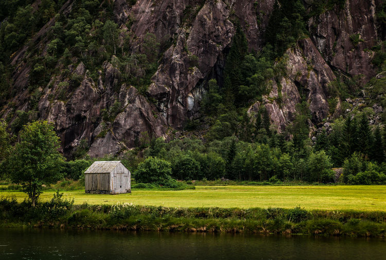 Small outhouse in a valley in West Norway. Nature Land Tranquility Day Mountain Grass No People Built Structure Tranquil Scene Green Color Landscape House Hut Valley River Farm Beauty In Nature Scenics - Nature Outdoors Water