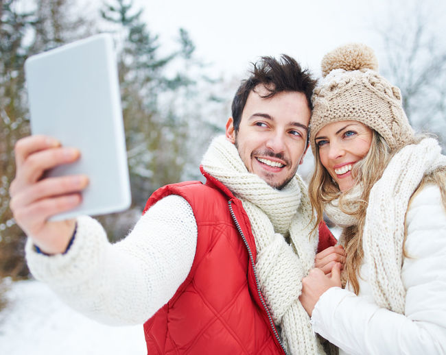 portrait of smiling young woman using smart phone in winter Adult Camera Cap Cheerfulness Chill Clothing Cold Temperature Communication Computer Content Couple Emotion Face Feel Good Fun Happiness Happy HEAD Holiday Joy Laughing Love Man Outdoors Outside PC People Photo Messaging Photograph Photographing Photography Photography Themes Portable Information Device Portrait Positive Emotion Scarf Season  Self Portrait Selfie Ski Holiday Ski Trip Smart Phone Smartphone Smile Smiling Snow Tablet Technology Together Tourists Vacation Warm Clothing Weather White Winter Winter Holiday Wireless Technology Woman Young Adult