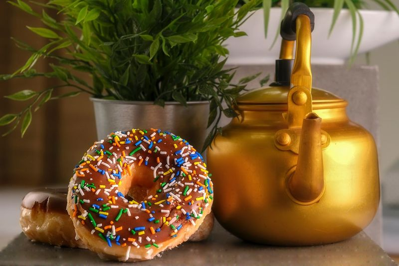 It's tea time with donuts No People Food Table Plant Indoors  Indulgence Sweet Food Dessert Focus On Foreground Multi Colored Freshness Food And Drink Close-up Baked Shape Still Life Sweet Decoration Sprinkles Potted Plant