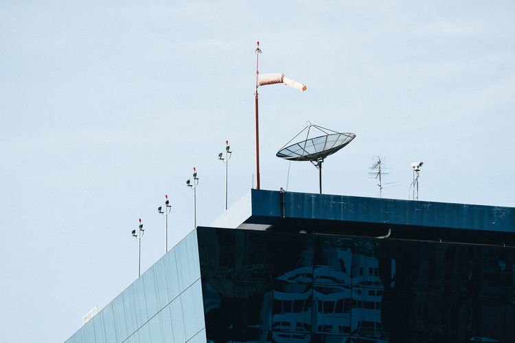 Low angle view of satellite dish and windsock on building terrace