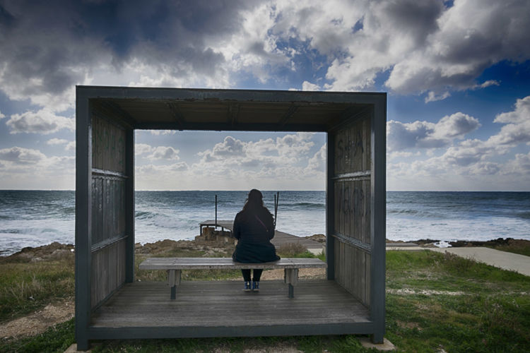 Rear view of woman sitting on bench in cabin at beach