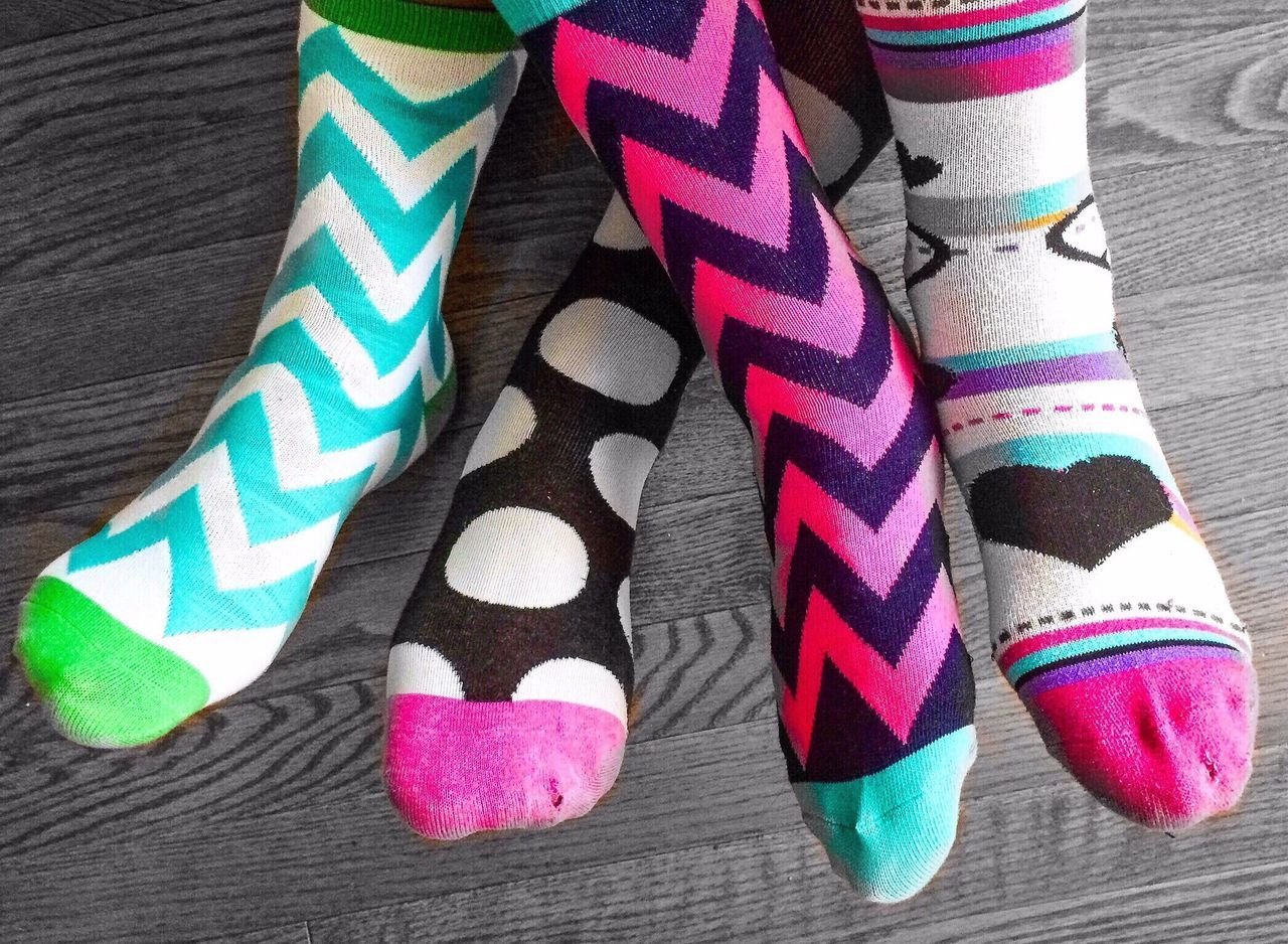 Low Section Of People Wearing Multi Colored Socks