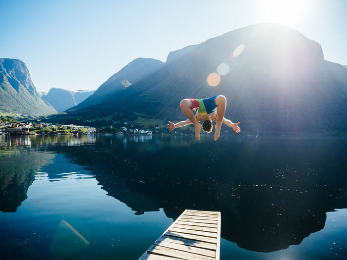 Young Man Diving Into Lake Against Mountain