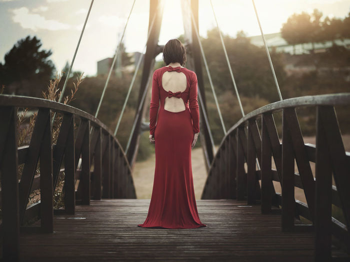 Dress Freedom Happiness Love Solitary Thinking Architecture Beautiful Woman Beauty Bridge Expression Lifestyles Modern Mysterious Outdoors Real People Rear View Red Relaxation Standing Thoughtful Women Young Women