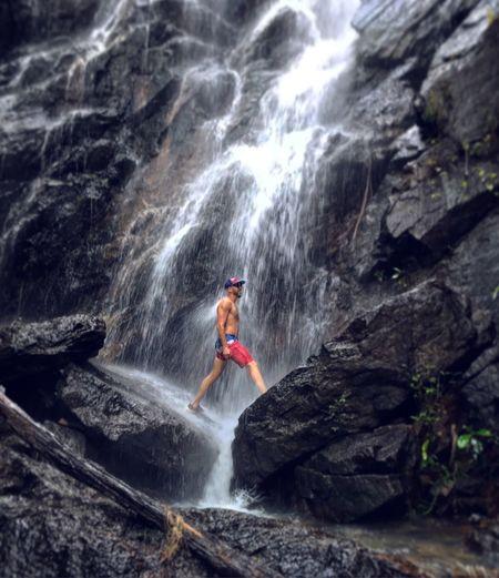 Man surfing on rock in waterfall