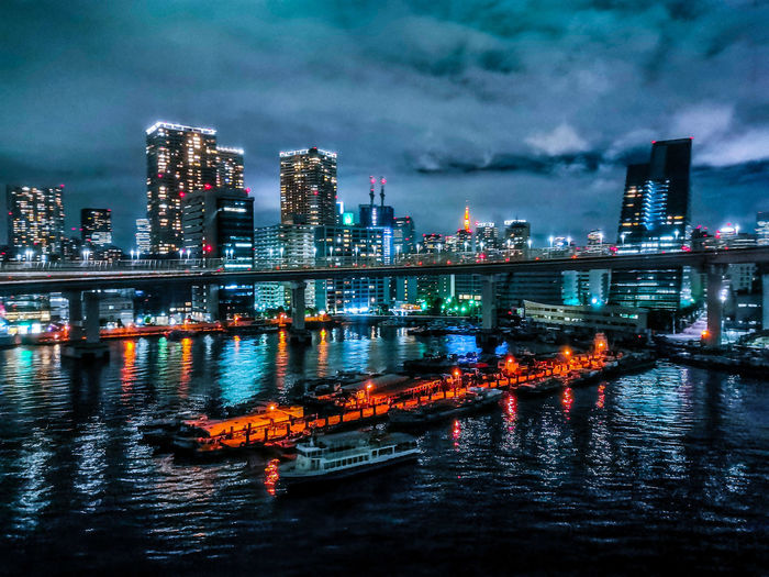 Illuminated city by river against sky at night