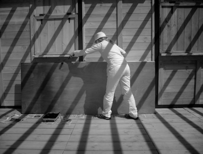 Full length of worker working on wooden door at workshop