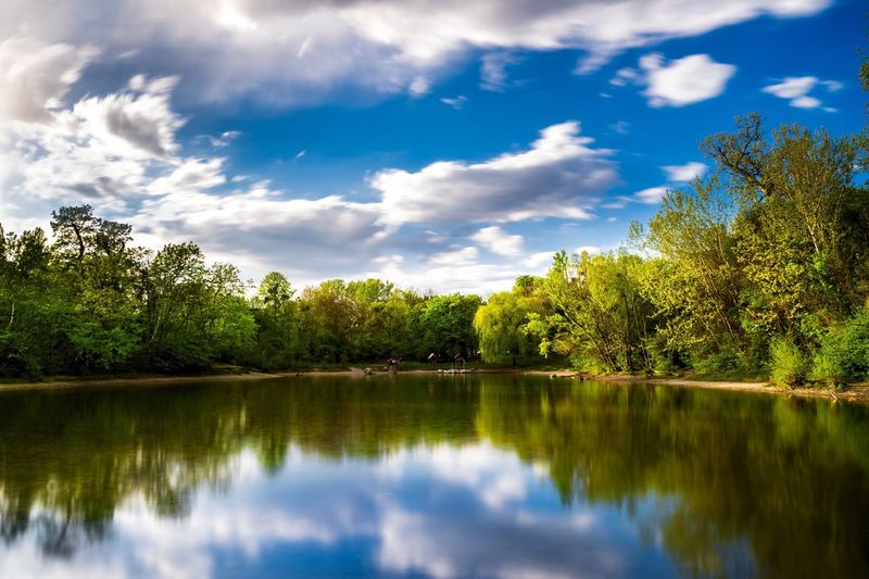 Idyllic shot of green trees reflection in lake against sky