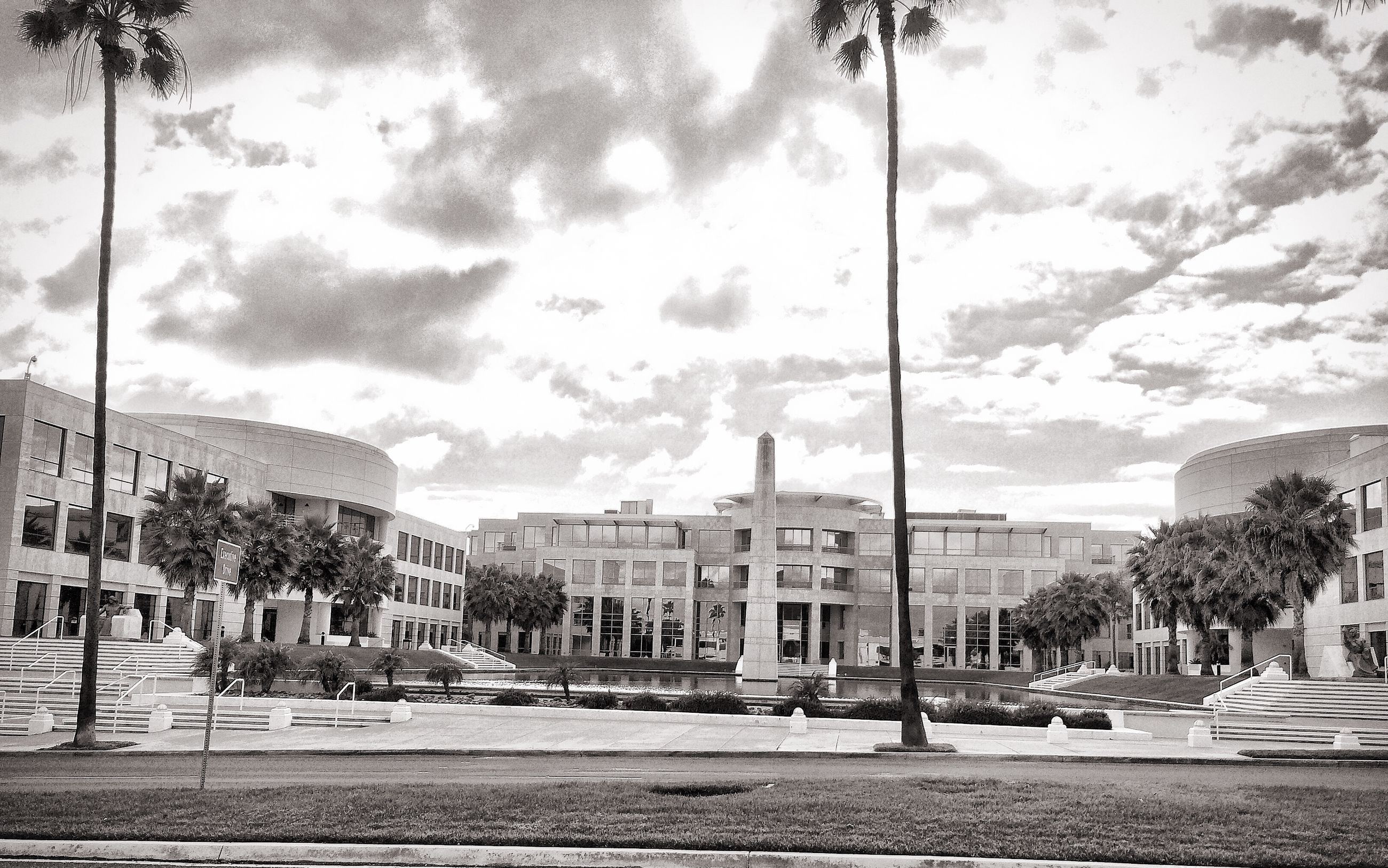 building exterior, sky, architecture, built structure, tree, street, cloud - sky, palm tree, city, street light, road, car, cloud, transportation, incidental people, cloudy, sidewalk, city life, the way forward, land vehicle