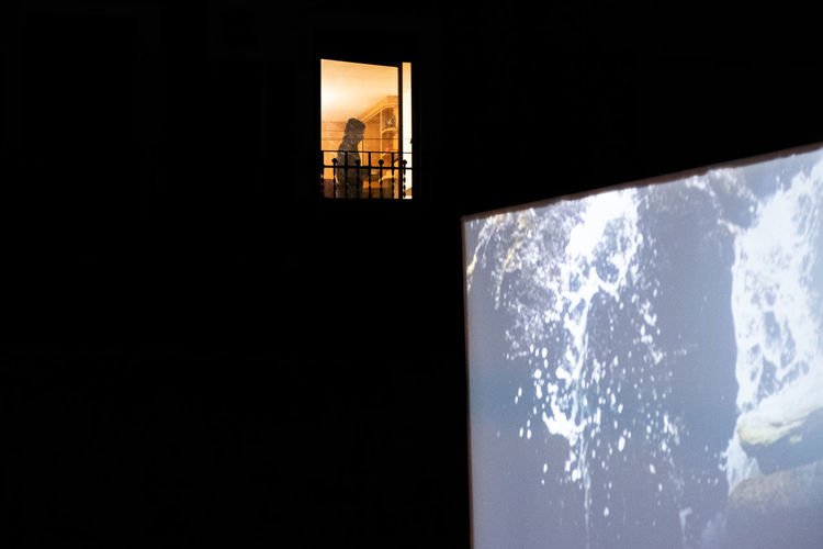 Low angle view of illuminated building against sky seen through window