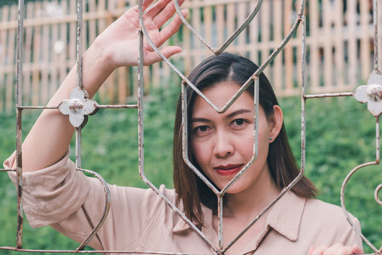 Portrait of young woman holding camera while standing by fence