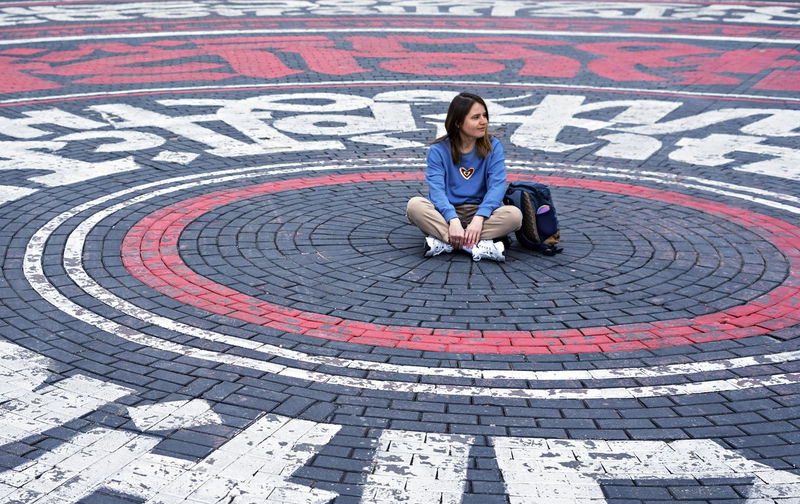 Young woman in blue sweatshirt alone sitting on street cobbled square in the form of circles