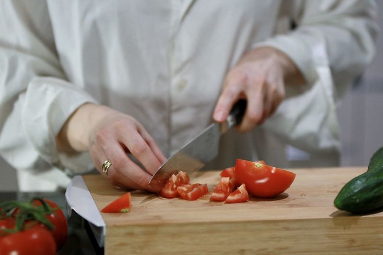 Midsection of man preparing vegetables on cutting board