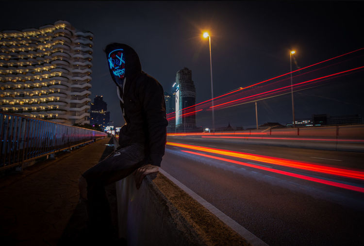 Man wearing mask sitting by light trails on bridge in city at night