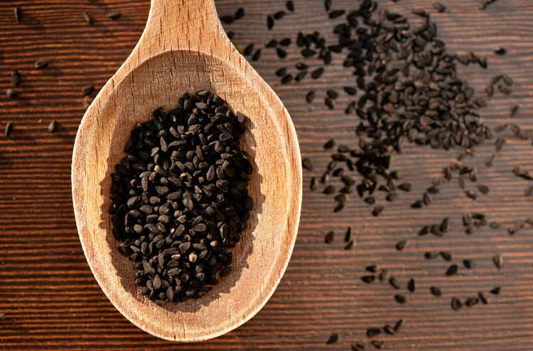 Black Nigella Sativa dry seeds portion on wooden spoon and spilled around food macro, Black cumin raw spice heap in day light, horizontal orientation, nobody. Polish name czarnuszka siewna. Black Black Cumin Close-up Cumin Directly Above Food Ingredient Nigella Sativa No People Seed Seeds Spice Spoon Studio Shot Wooden Spoon