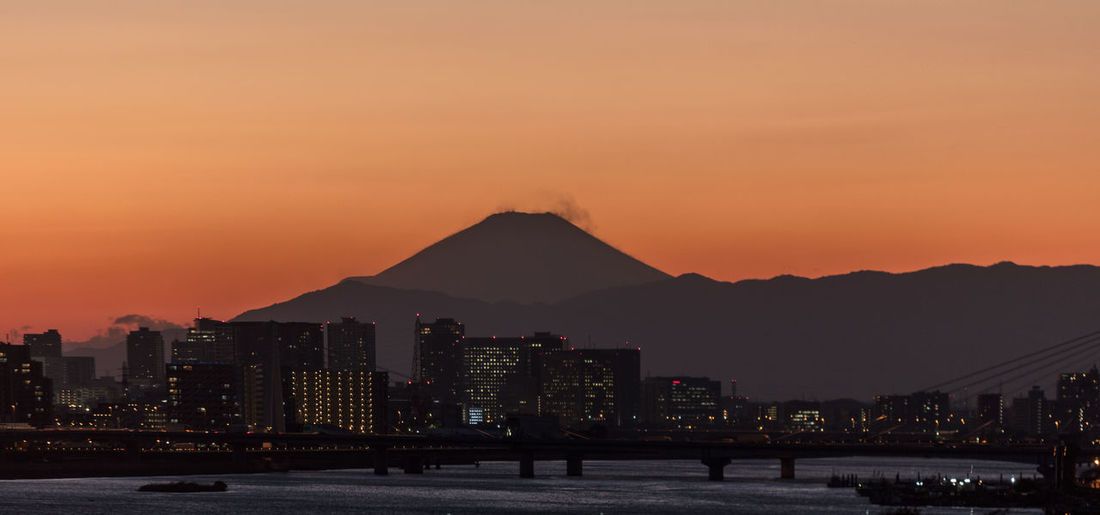 mount fuji under a tokyo sunset ASIA Japan Mount FuJi Tokyo Architecture Beauty In Nature Building Building Exterior Built Structure City Cityscape Illuminated Landscape Mountain Nature No People Office Building Exterior Orange Color Outdoors Sky Skyscraper Sunset Travel Destinations Water Waterfront