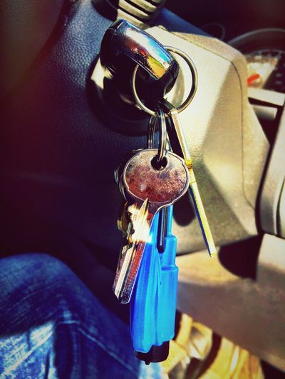 A car key plugged into a car ignition. Close Up Steering Console Ignition Car Key Hanging Close-up Chain Indoors  Real People Key Ring Key Metal