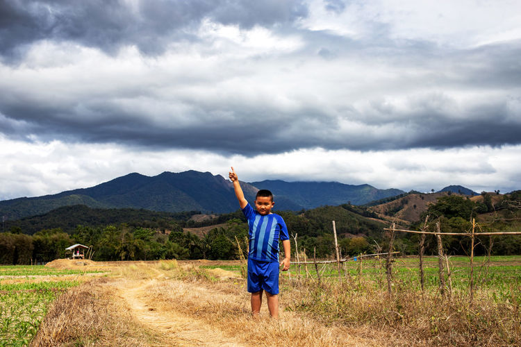 Portrait of boy pointing while standing on grass against sky