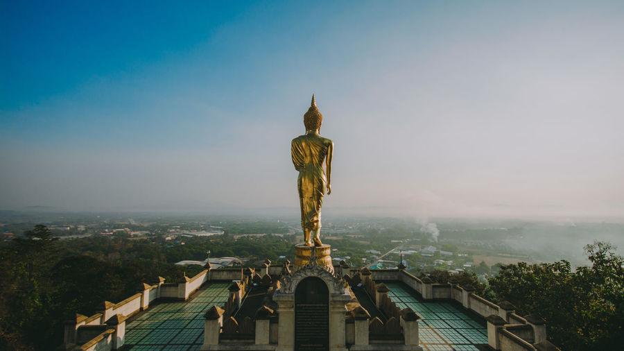 Statue on building against landscape