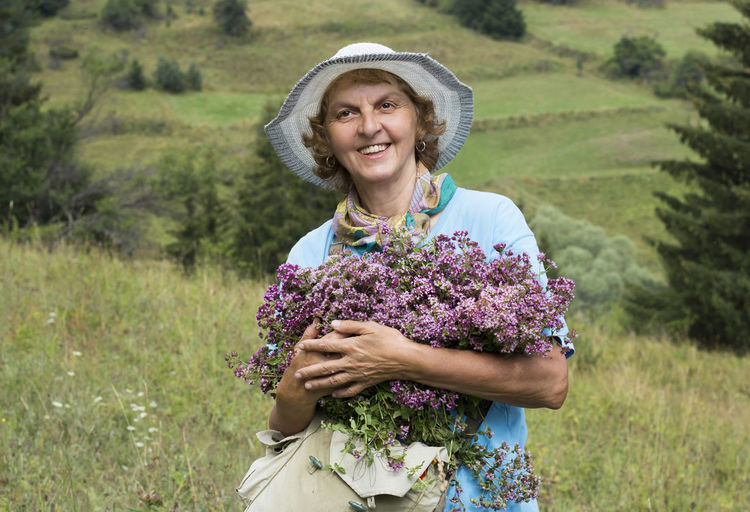 Portrait of a smiling young woman with oregano herbs flowers in her hands, beautiful nature