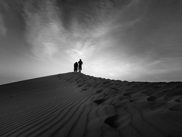 Men standing on sand dune against sky