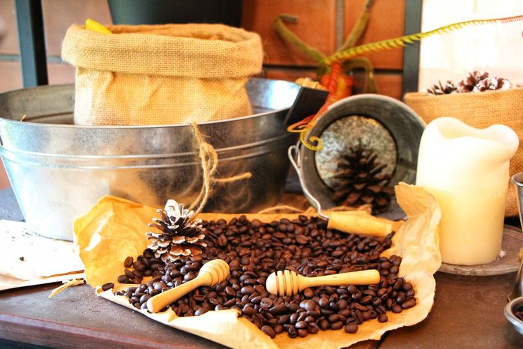 Close-up of coffee beans by burlap and candle on table