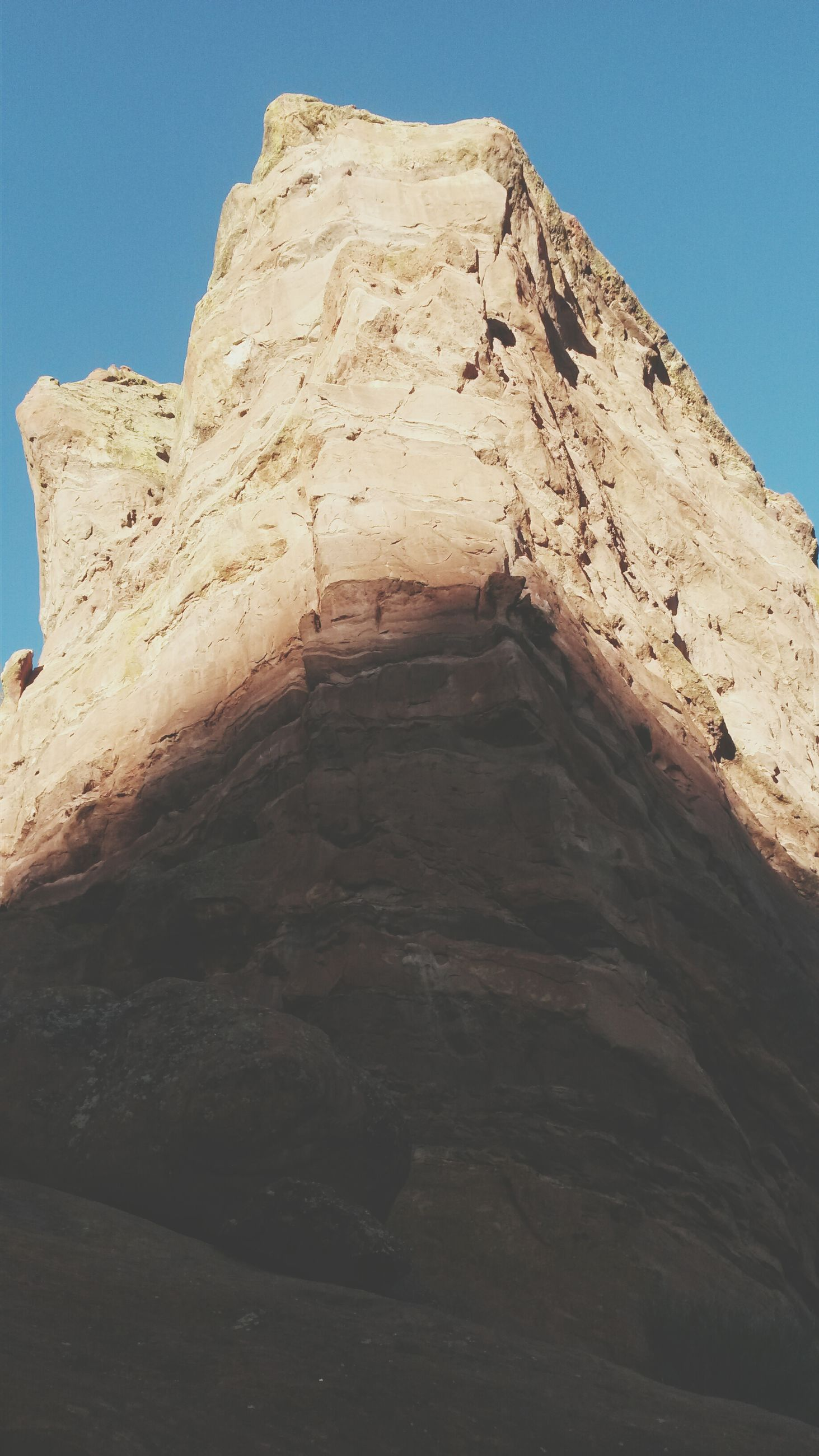 clear sky, low angle view, built structure, architecture, blue, building exterior, sunlight, copy space, day, no people, rock - object, rock formation, outdoors, wall - building feature, textured, stone wall, old, sky, shadow, nature