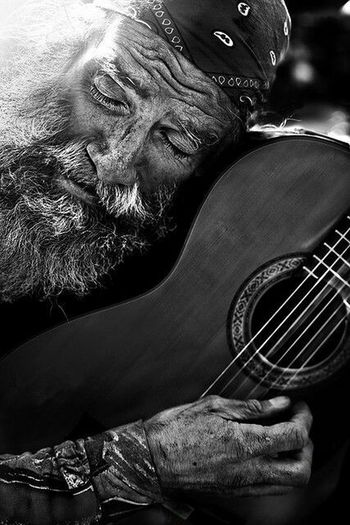 He may be old...he may be in poor health...he may even be homeless...but he hasn't let any of those factors rob him of his passion in life...he still plays his beloved guitar! Portrait Black & White Man With His Guitar Powerful Face Intense Passion People Photography Around The World